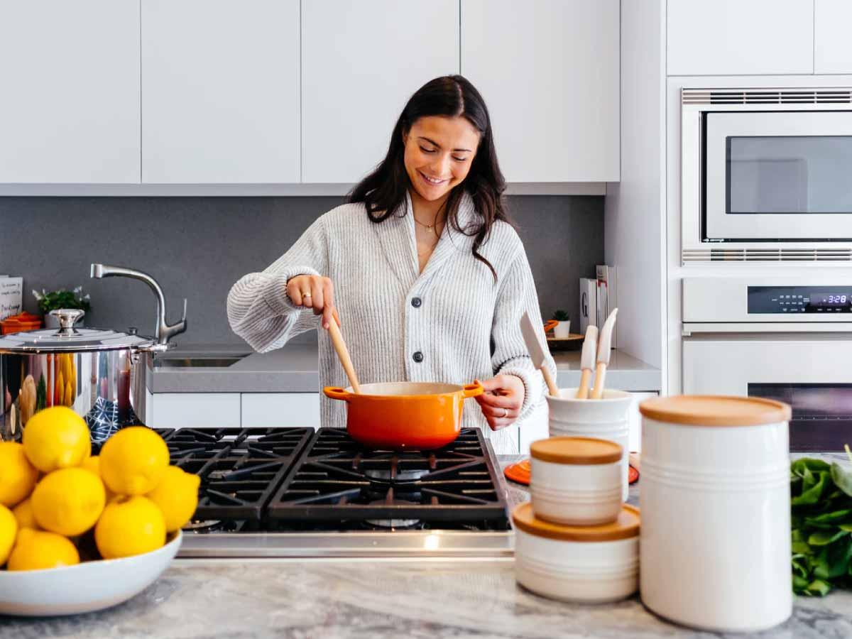 Mujer cocinando en una cocina blanca con ollas
