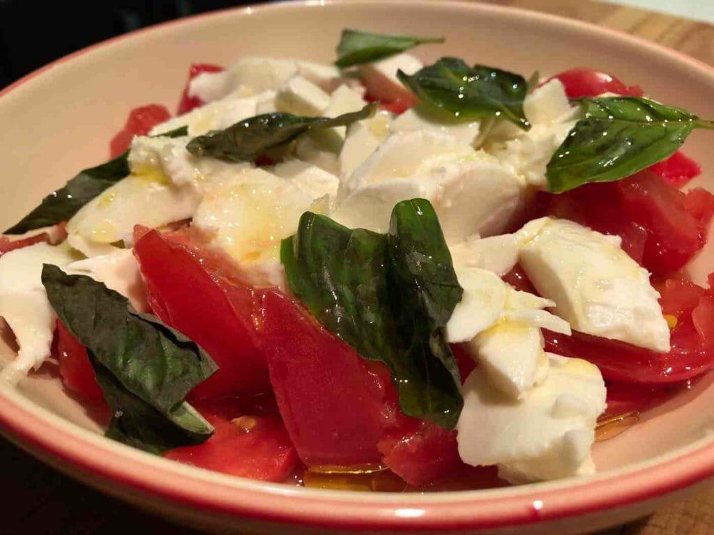 Presentación de una ensalada caprese de tomate y mozzarella
