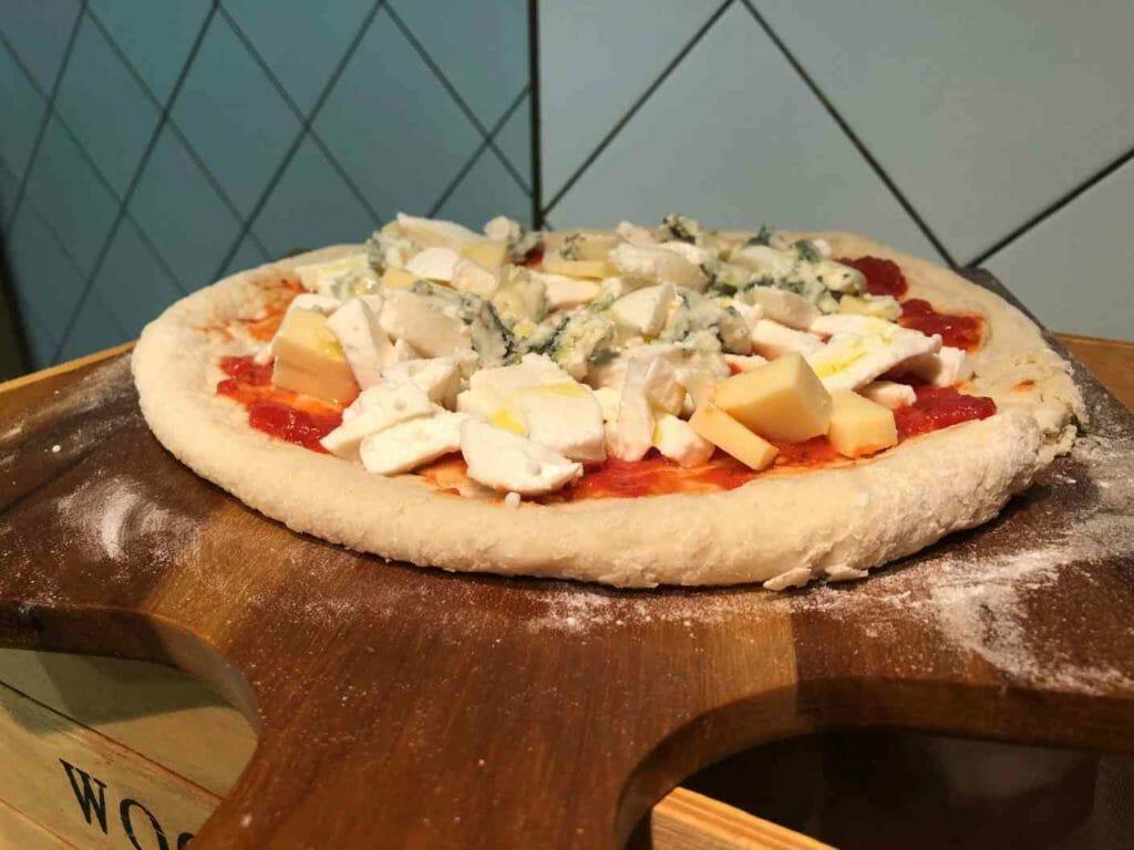 Pizza napolitana con los ingredientes repartidos antes de hornear