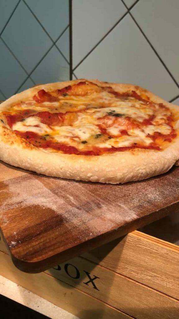 Pizza casera en horno eléctrico recién horneada, en una pala de madera.